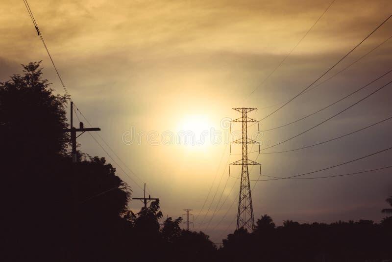 Torre eléctrica de alto voltaje el tiempo de la puesta del sol y cielo en sunse imagenes de archivo