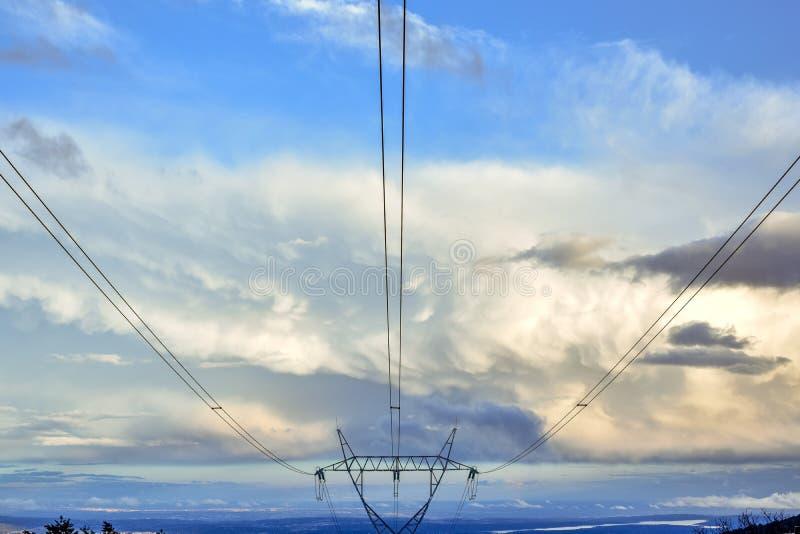 Torre eléctrica en cielo azul con las nubes en la puesta del sol foto de archivo