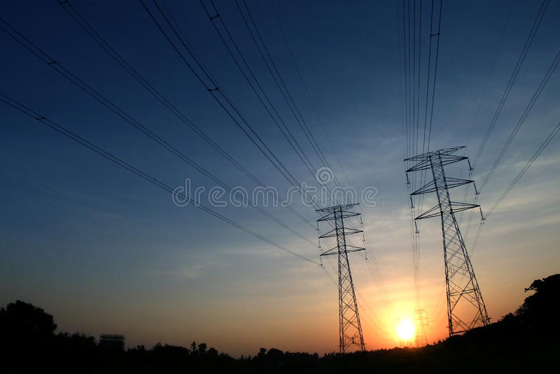 Torre elétrica com fio na silhueta preta no amanhecer, tiros largos da lente de olho imagem de stock