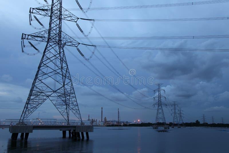 Torre elétrica no mar através da propriedade industrial foto de stock royalty free