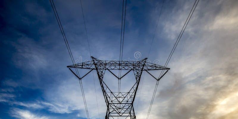 Torre elettrica contro un cielo nuvoloso blu scuro fotografia stock