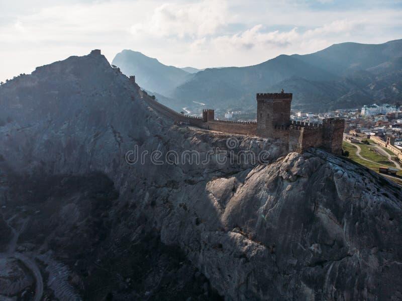 Torre genovese medievale antica della fortezza sulle rocce della catena montuosa sopra il mare, vista aerea dal fuco fotografia stock