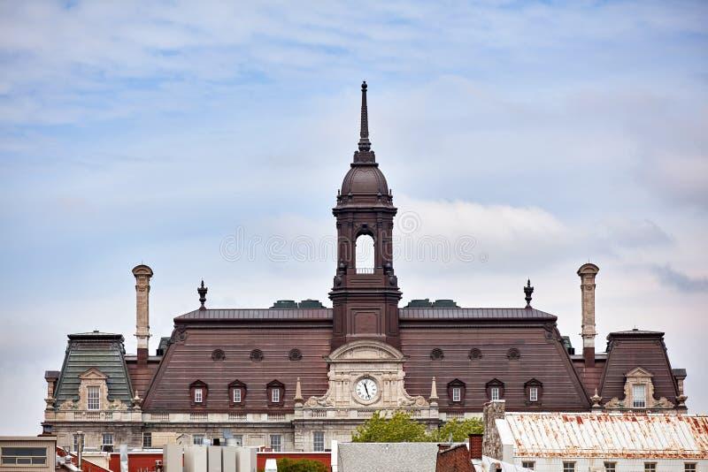 A torre, o pulso de disparo e o telhado da câmara municipal hotel de ville de Montreal contra o céu nebuloso brilhante em Montrea imagens de stock