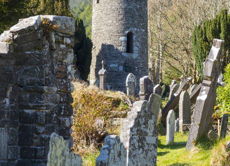 A torre redonda antiga no cemitério no local monástico histórico de Glendalough no condado Wicklow na Irlanda fotos de stock royalty free