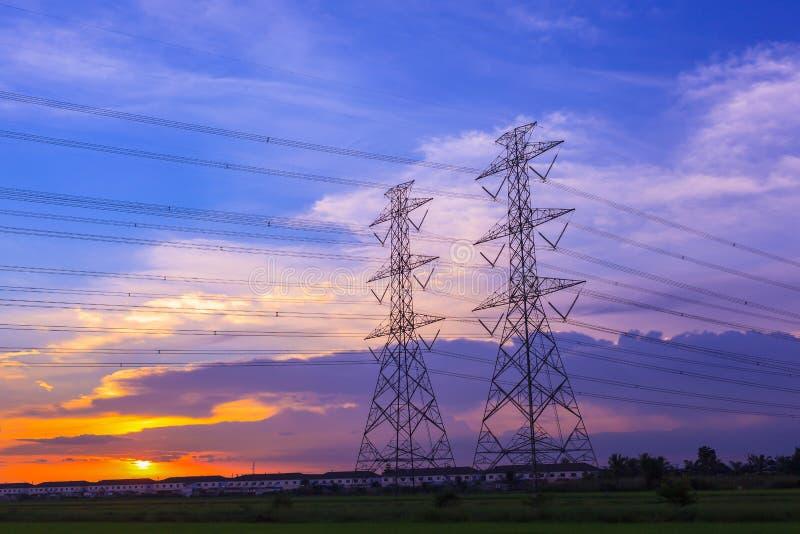 Torre y línea eléctrica de alto voltaje de los posts en fondo del cielo de la puesta del sol foto de archivo