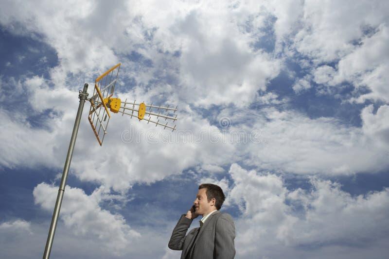 Torre y nubes por satélite de Using Cellphone Against del hombre de negocios fotografía de archivo