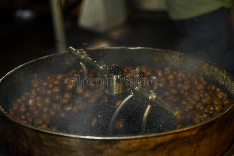 Torrefazione matta della castagna per il cibo in un tamburo di tornitura fotografia stock libera da diritti