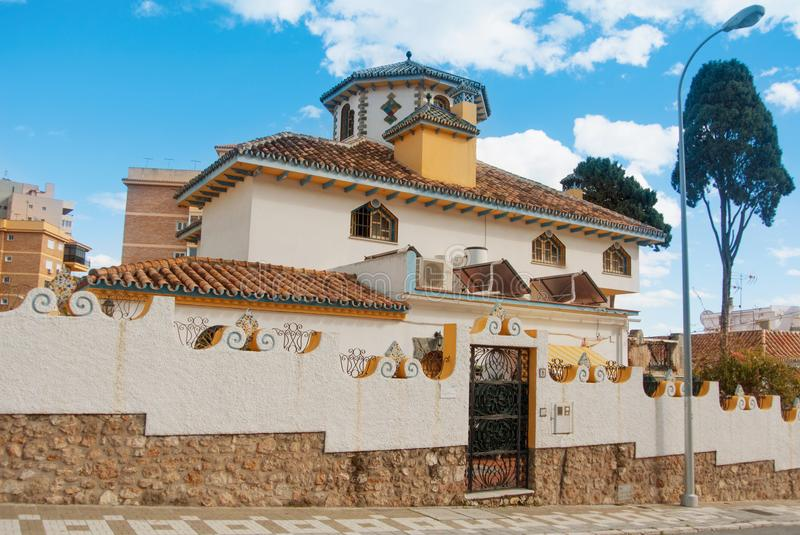 TORREMOLINOS, SPAIN - FEBRUARY 13, 2014: Beautiful decorated white typical mediterranean spanish house with high stone fence, a s stock images