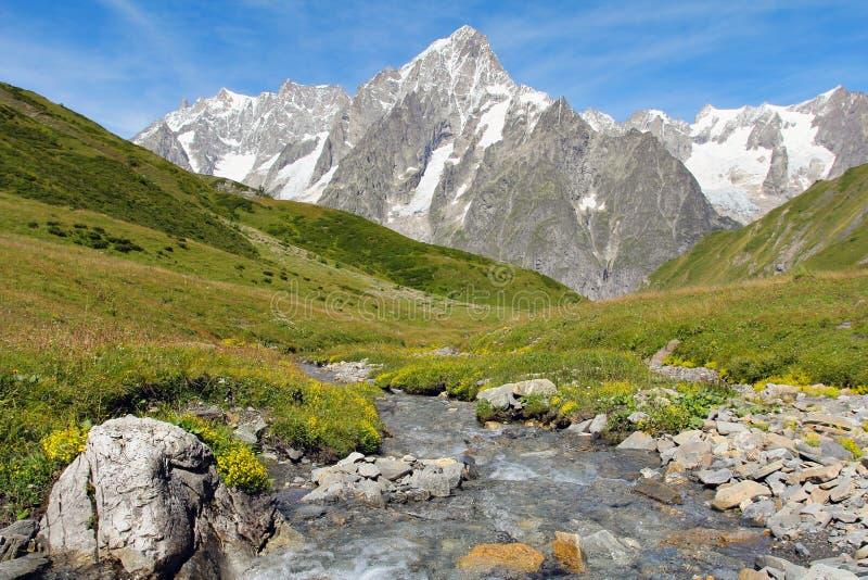 Torrente montano con il grande ghiacciaio di Jorasses immagini stock