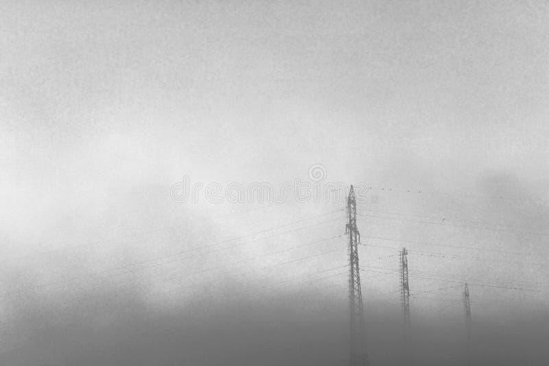 Torres de alto voltaje en el humo de un fuego fotos de archivo libres de regalías