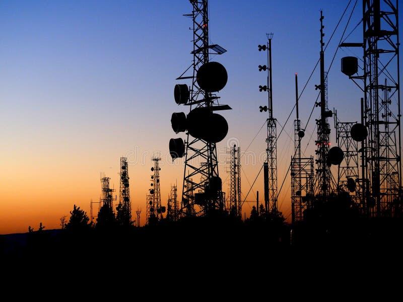 Torres de comunicación de la cima de la montaña en la puesta del sol fotos de archivo