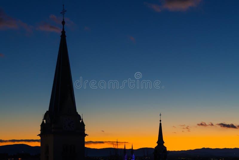 Torres de iglesia católica en un fondo de igualación azul anaranjado maravilloso del cielo imagen de archivo libre de regalías