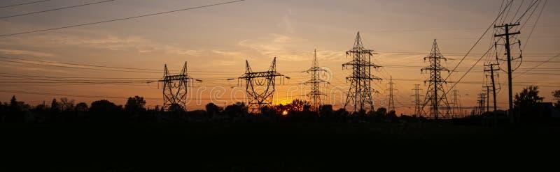 Torres de la corriente eléctrica en la puesta del sol imágenes de archivo libres de regalías