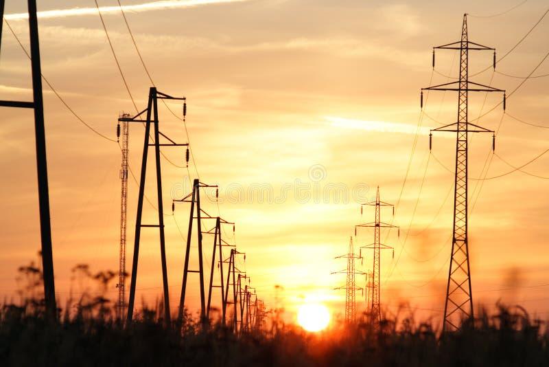 Torres de la electricidad en la puesta del sol fotografía de archivo