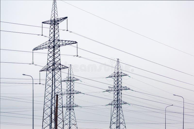Torres de la línea eléctrica con los alambres contra un cielo nublado imagen de archivo