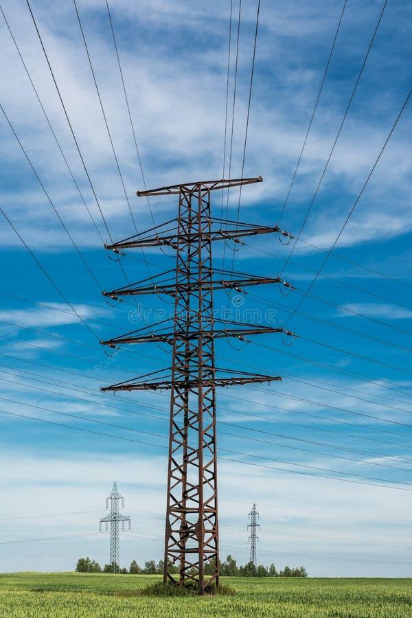 Torres de la transmisión en campo de grano verde imagen de archivo