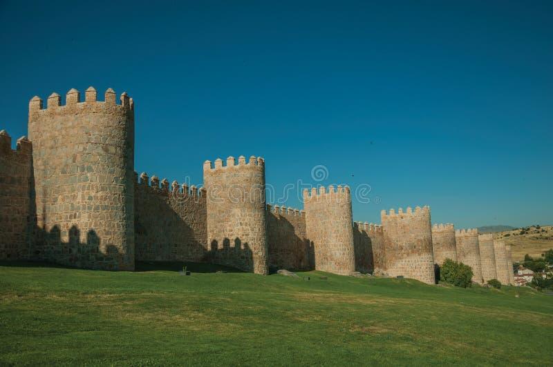 Torres de pedra na parede da grande cidade e no gramado verde em Avila fotos de stock