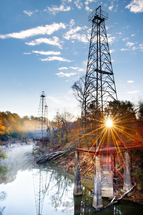 Torres de perforación de petróleo del resplandor solar fotografía de archivo