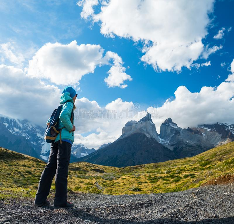 Torres del Paine National Park. Woman hiker stands on the trail and enjoys the view of the mountains in Torres del Paine National Park, Chilean Patagonia royalty free stock photos