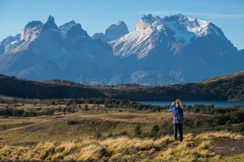 Torres del Paine National Park. Woman hiker takes picture of the Cordillera Paine mountains in the Torres del Paine National Park in Chile royalty free stock image