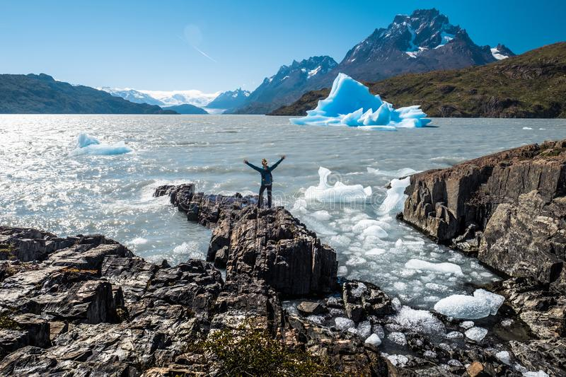 Torres del Paine National Park. Young woman stands on the rocky coast of the Grey Lake with raised hands and enjoys the blue iceberg view. Torres del Paine royalty free stock photo