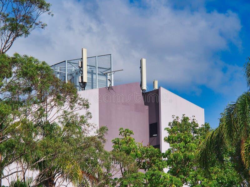 Torres del teléfono móvil en un edificio coloreado de color de malva fotografía de archivo libre de regalías