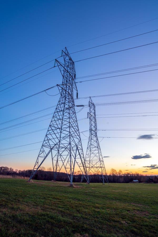 Torres e fios da distribuição da eletricidade no crepúsculo fotos de stock