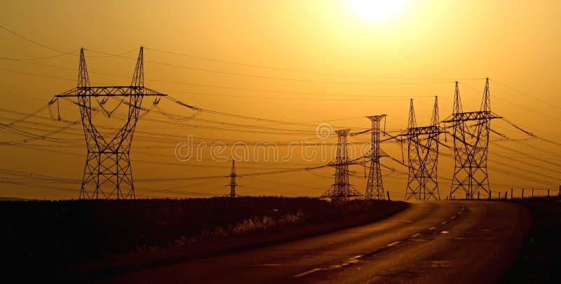 Torres eléctricas de alto voltaje durante puesta del sol fotografía de archivo