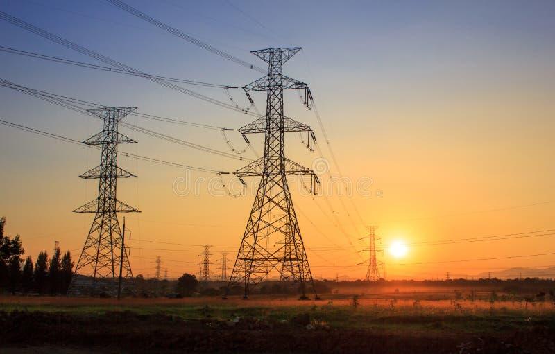 Torres eléctricas de alto voltaje durante puesta del sol imágenes de archivo libres de regalías