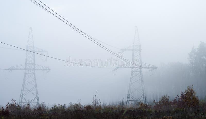 Torres eléctricas de alto voltaje en la niebla contra la perspectiva del bosque fotos de archivo libres de regalías