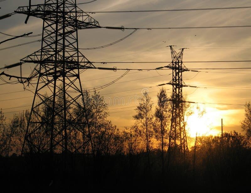 Torres eléctricas de alto voltaje en la puesta del sol foto de archivo libre de regalías