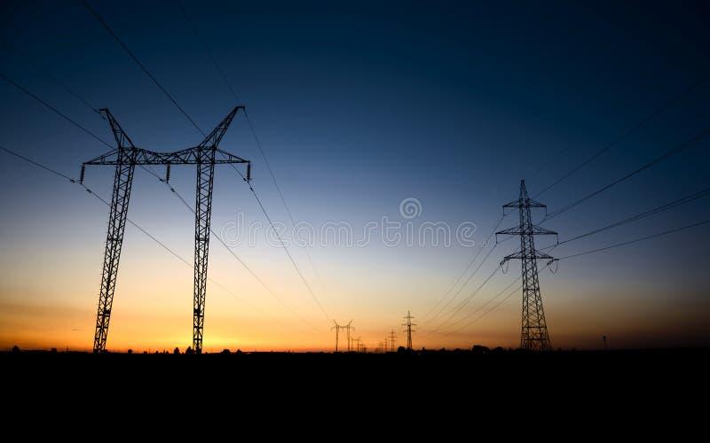 Torres grandes de la transmisión en la hora azul fotografía de archivo libre de regalías