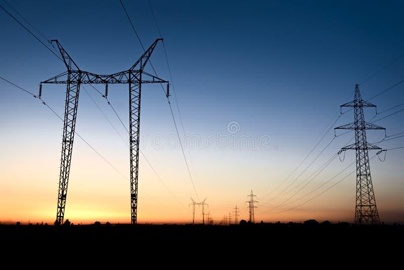 Torres grandes de la transmisión en la hora azul fotografía de archivo