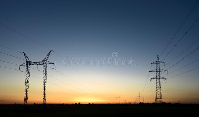 Torres grandes de la transmisión en la puesta del sol imagen de archivo