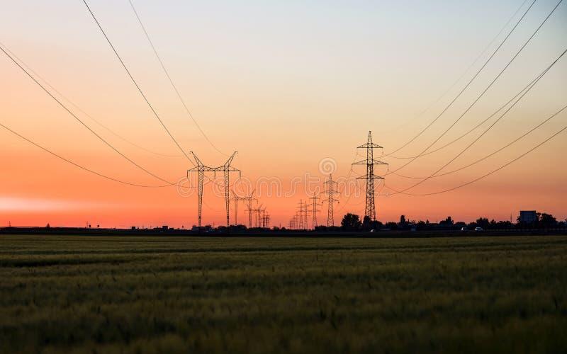 Torres grandes de la transmisión en la puesta del sol fotos de archivo libres de regalías
