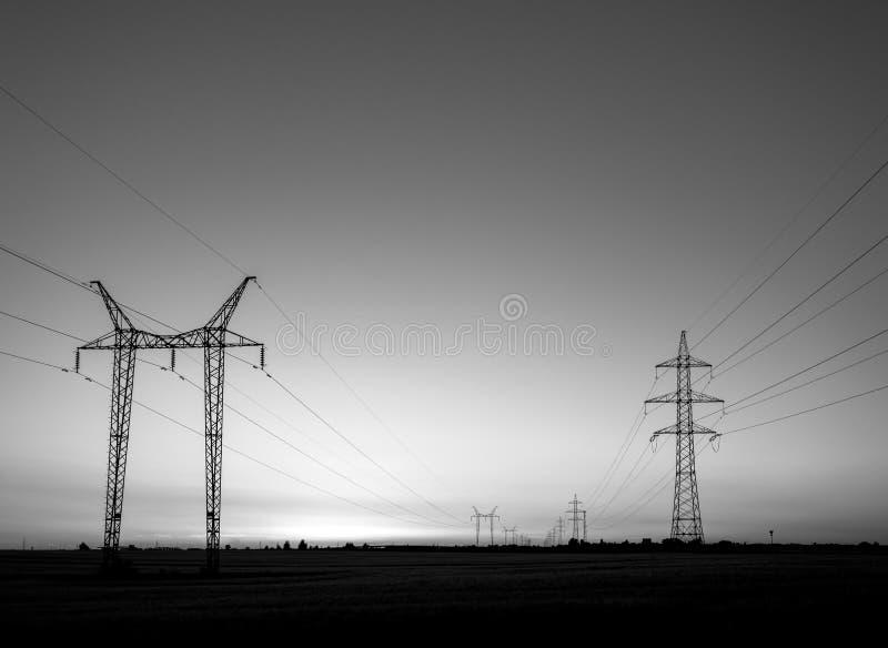 Torres grandes de la transmisión en la puesta del sol imagenes de archivo