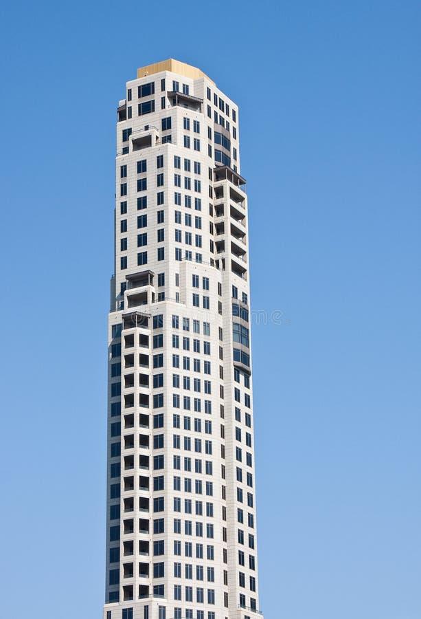 Torretta concreta grigia dell'ufficio che aumenta nel cielo blu fotografia stock libera da diritti