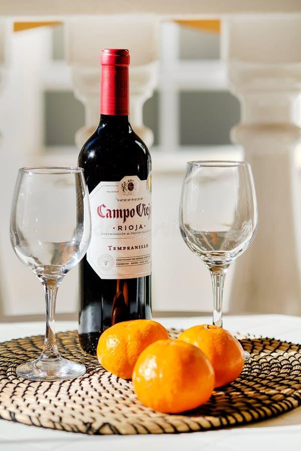 Torrevieja, Испания - 11-ое апреля 2019: Близкая поднимающая вверх бутылка Campo Viejo Rioja 2 пустых ясных бокала и 3 апельсина стоковая фотография rf