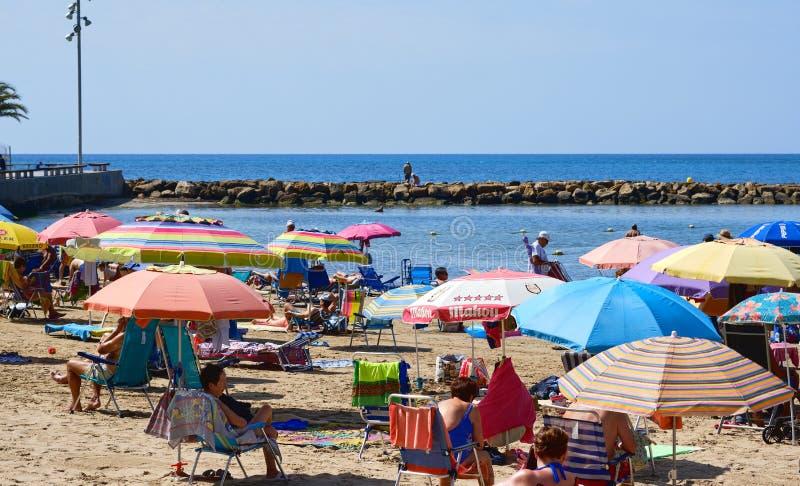 Torrevieja, Испания - 10-ое июня 2019: Серия sunbath туристов людей на популярном пляже Playa del cura в курортном городе Torrevi стоковая фотография rf