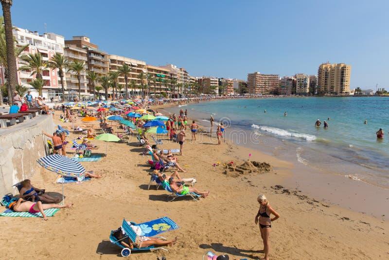 Torrevieja Spanje met toeristen en bezoekers op het mooie strand in de Oktober-zon stock foto