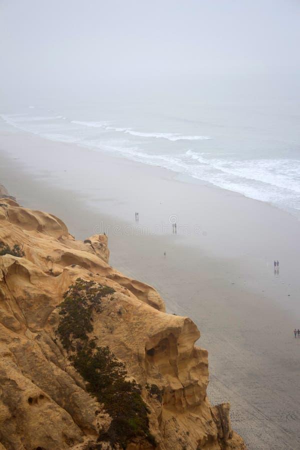 Torrey Pine状态储备,从峭壁上面的拉霍亚,加利福尼亚海景与走在下面海滩的人在阴天 免版税图库摄影
