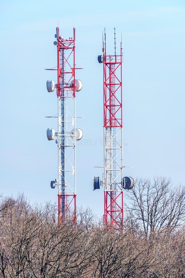 Torri cellulari di comunicazione su mezzi mobili nella foresta di primavera sul fondo del cielo blu Paesaggio verticale fotografia stock libera da diritti