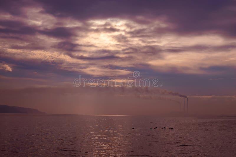 Torri della centrale elettrica dal lago immagini stock