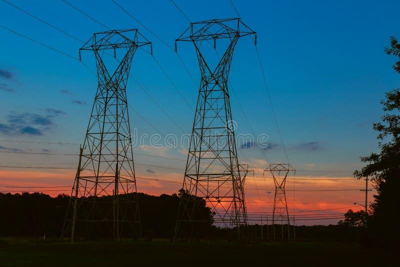 Torri di comunicazione del cavo di elettricità sull'allungamento di tramonto fotografie stock libere da diritti