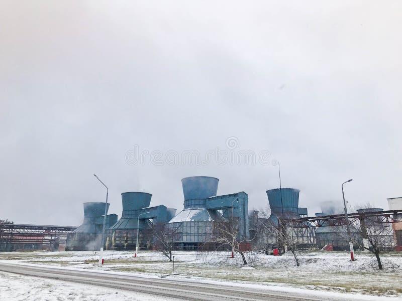 Torri di raffreddamento chimiche del grande ferro blu del metallo, attrezzatura di potere con fumo, vapore ad una raffineria, cen immagini stock