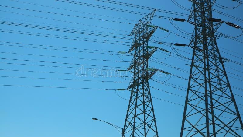 Torri gemellate del trasporto di energia un giorno soleggiato immagine stock