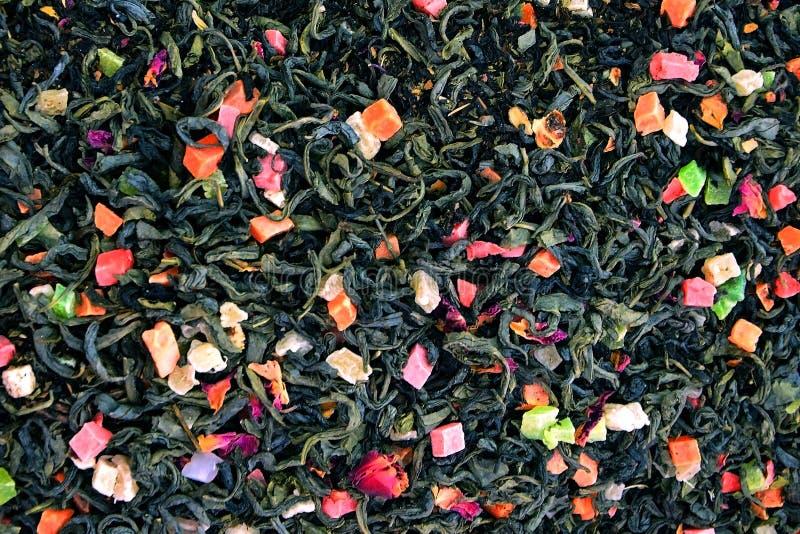 Torrt grönt te med blommor och stycken av frukt bakgrund av den bästa sikten för te royaltyfri bild
