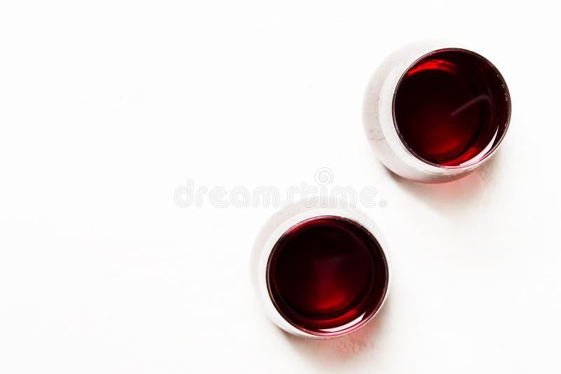 Torrt rött vin i exponeringsglas på en vit bakgrund, bästa sikt arkivbilder