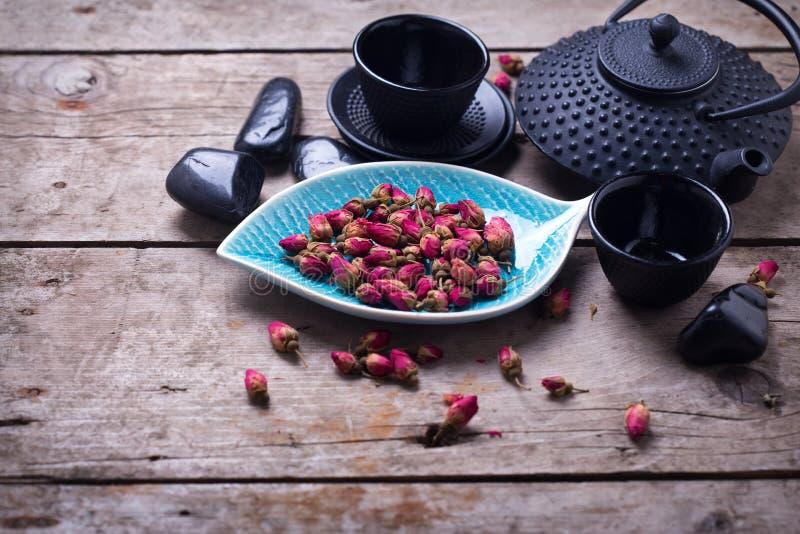 Torrt rosa te i bunke och den traditionella asiatiska teservisen på åldrigt uppvaktar arkivbild