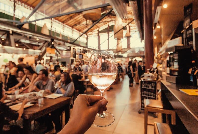 Torrt vin i exponeringsglas av den hungriga turisten inom folkmassamatmarknad med snabbmatdiversehandel och tabellen för att äta, royaltyfri fotografi